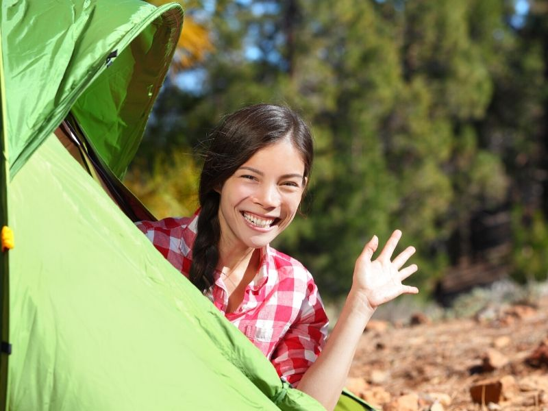 Girl waving from tent